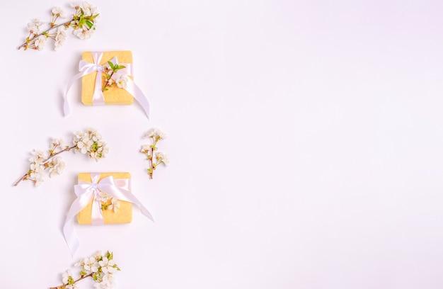 白い背景とコピースペースにギフト用のボックスと開花桜の枝。フラットレイ、3月8日、母の日、バナー。上から見る