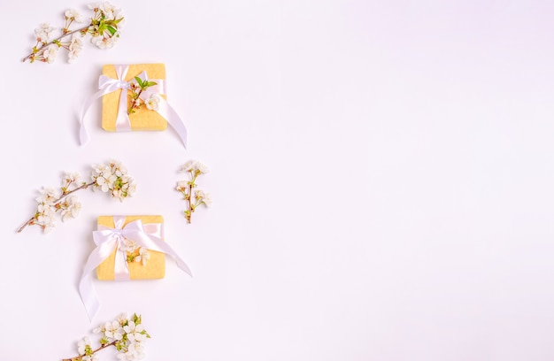 Blossoming cherry branches with boxes for gifts on a white background and copy space. flat lay, 8 march, mother's day, banner. view from above