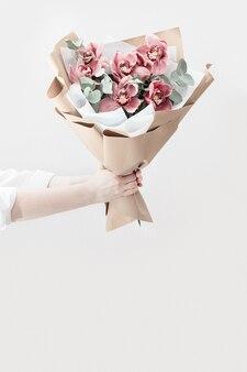 女性の手でピンクの蘭の繊細な花の花束を開花
