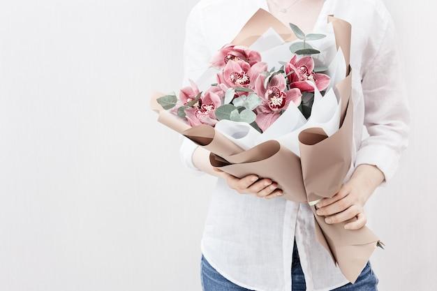 여성의 손에 분홍색 난초의 꽃이 만발한 섬세한 꽃 프리미엄 사진