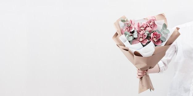 여성의 손에 분홍색 난초의 꽃이 만발한 섬세한 꽃