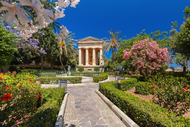 Blossoming spring lower barrakka gardens and monument dedicated to alexander ball in the old town valletta, capital of malta.