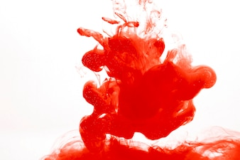 Blot of red paint in water