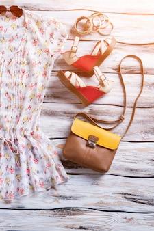 ブラウス、ウェッジサンダル、ブレスレット。財布とカラフルなブレスレット。展示されている女性のファッショナブルな衣装。新しいカラフルなデザイン。