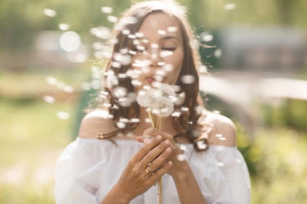 Красивая расплывчатая девушка дуя на одуванчике на камере. симмер время красивая женщина на улице с blowball