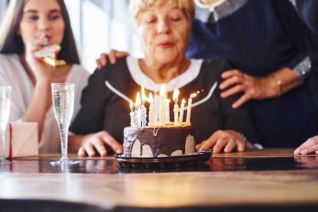 Blowing the candles. senior woman with family and friends celebrating a birthday indoors.
