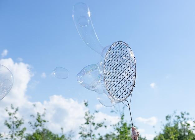 Дует большие мыльные пузыри на фоне голубого неба