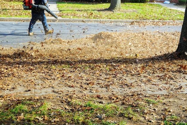 Сдувая падающие с деревьев листья у человека с помощью воздуходувки, работает уборщица