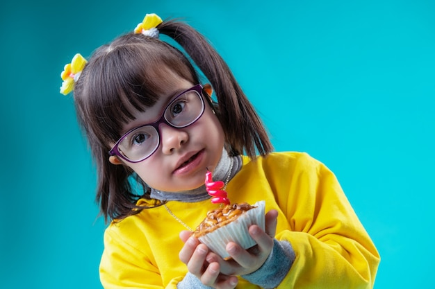 Blowing out candle. child with big brown eyes having mental disorder and unusual face features