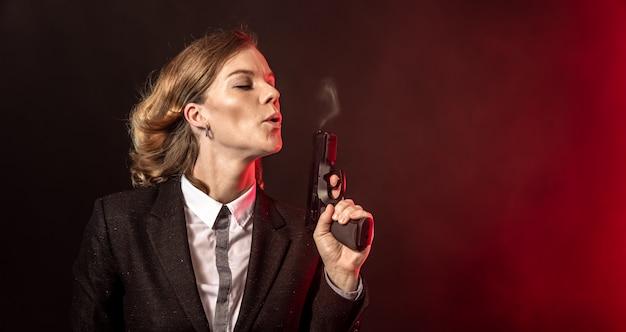 Выдувание дыма из ружья после выстрела. портрет деловой женщины на темном фоне. баннер с копией пространства