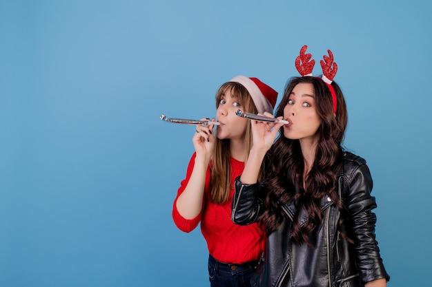 クリスマスのblowingを吹く女性と青で分離されたクリスマス帽子をかぶっている女性