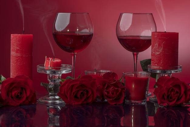 Задутые красные свечи в прозрачных подсвечниках с вином в окружении роз