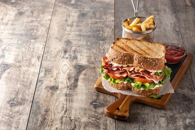 木製のテーブルにベーコン、レタス、トマトのbltサンドイッチ
