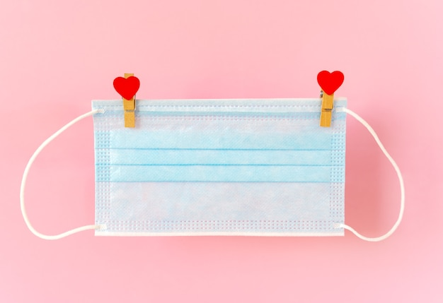 Blu protective face mask hanging on clothespins with hearts on rope.