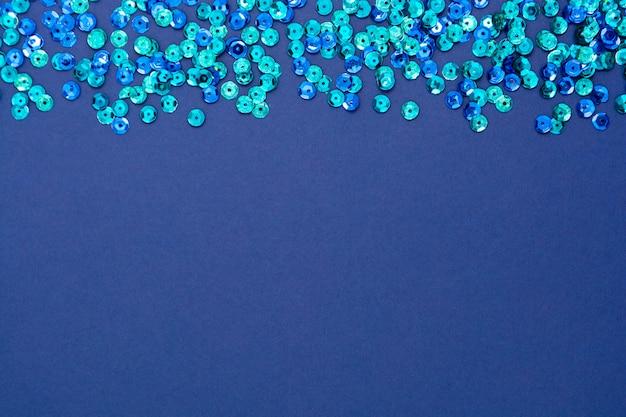 青の抽象的な背景、丸い青いスパンコールのテクスチャ。テキスト用のスペースとモックアップのクリスマスやパーティーの創造。