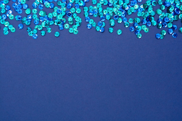 Blue abstract background, texture with round blue sequins. christmas or party creative mock up with space for text.