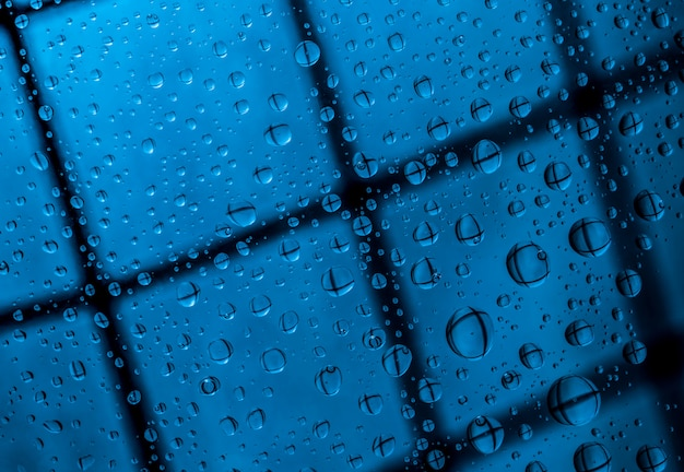 Blue abstract blur background with water drops and reflection on transparent glass. blue background for lonely, sad and missing someone on rainy day concept