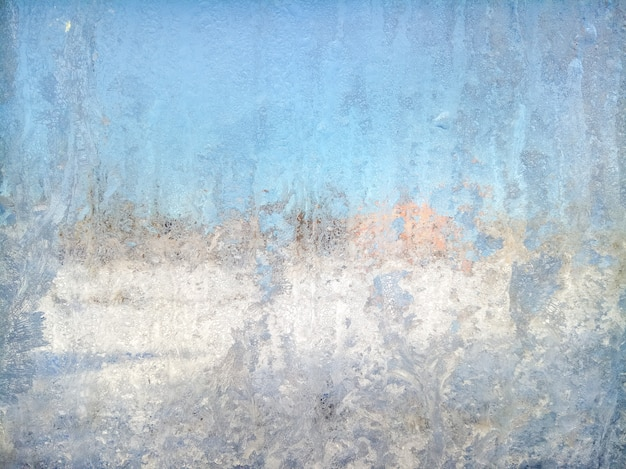 Blue abstract blurred background with a winter window covered with a frosty texture.