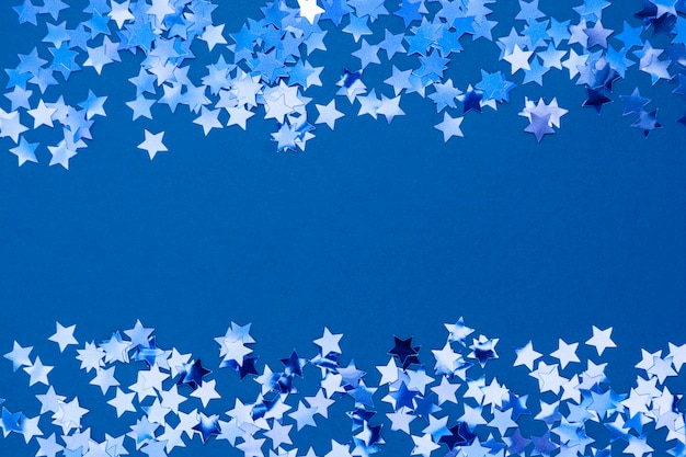 Blue abstract christmas background border, frame texture with stars confetti on blue background. space for text.