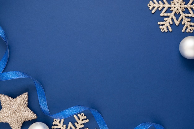 Blue abstract christmas minimalistic styled background with silver snowflakes, baubles and blue ribbon. blue mock up with space for text.