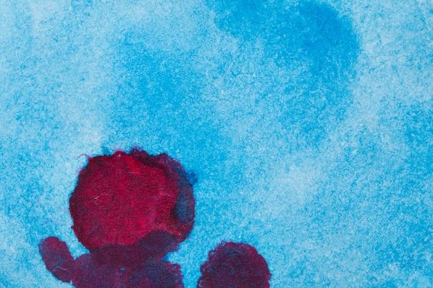 赤い汚れ水彩インク背景と青の抽象