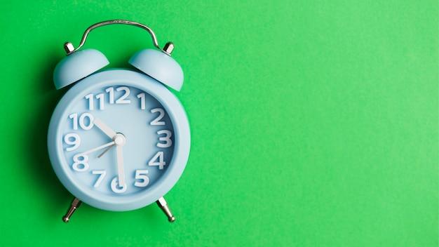 Синий будильник на зеленом фоне