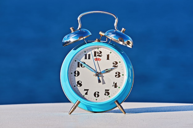 Blue alarm clock against sea, as spring forward and daylight saving concep