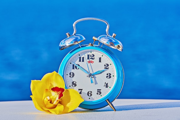 Blue alarm clock against sea background as spring forward and daylight saving concep