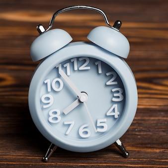 Blue alarm clock against wooden textured background