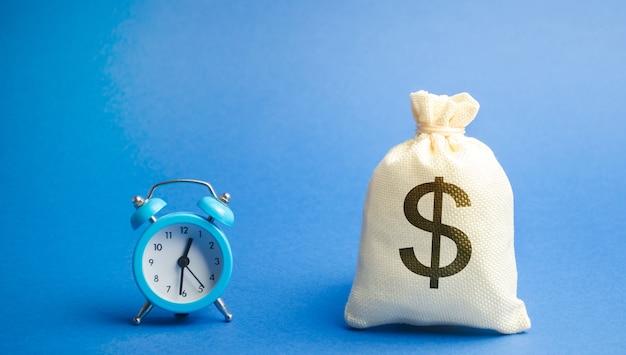 블루 알람 시계와 돈 가방. 대출, 신용, 모기지 개념. 예금, 돈 투자.