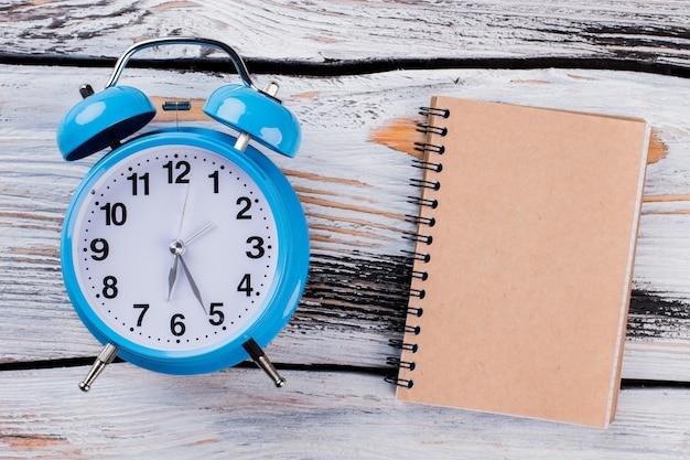 Синий будильник и блокнот на белом дереве. концепция управления временем.