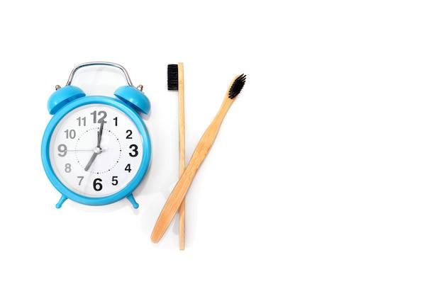 Синий будильник и две бамбуковые зубные щетки, изолированные на белом фоне. скопируйте пространство.