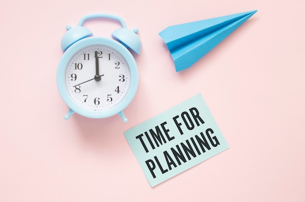 Blue alarm clock, blue paper plane and time for planning blue post it on light pink background