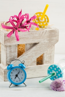 Blue alarm clock, bottles with pink lilly