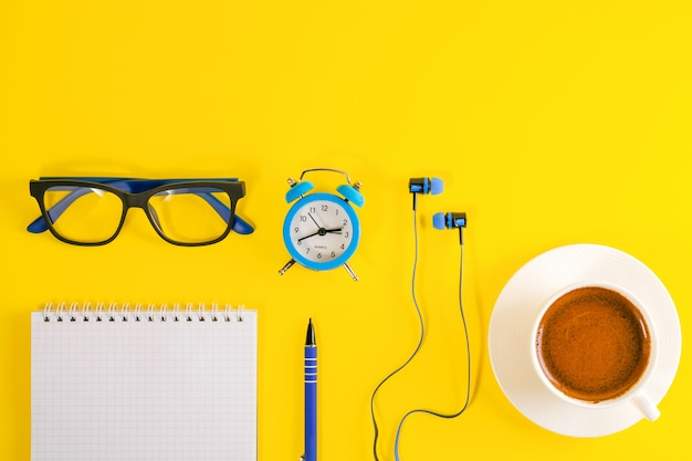 Blue alarm clock, earphones, eyeglasses and note book with pen, on yellow background. coffee cup.