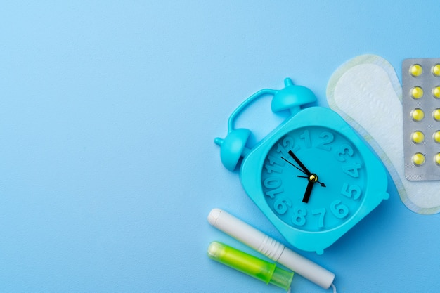 Blue alarm clock, female hygienic pad and tampon, top view