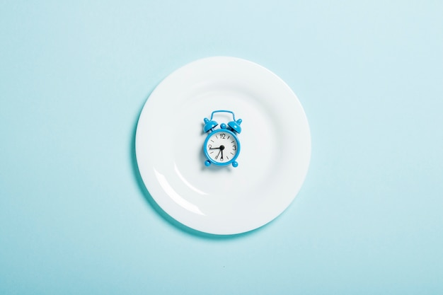 Blue alarm clock lies on a white plate on a blue wall. concept of diet, meal schedule, weight loss. flat lay, top view