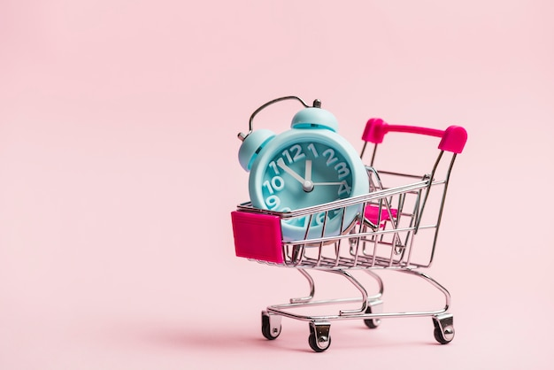 Blue alarm clock in the miniature shopping trolley