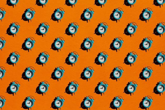 Синий будильник на оранжевом фоне. шаблон.