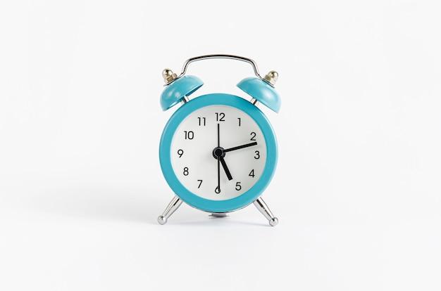 白い壁に青い目覚まし時計。時間と締め切りのコンセプト