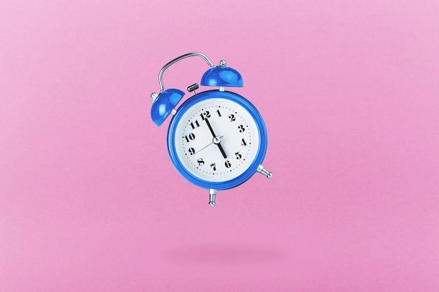 Blue alarm clock on pink surface
