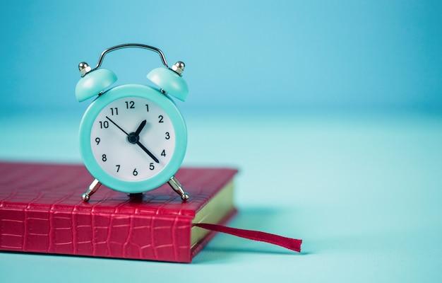 파란색 배경에 파란색 알람 시계, 빨간색 메모장. 시간 계획의 개념. 확대. 텍스트를위한 빈 공간입니다.