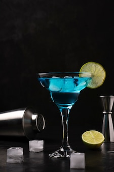 블루 알콜 칵테일은 검정에 얼음 잔에 서 있습니다.