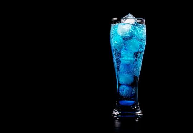 Синий алкогольный коктейль с кубиками льда стоит в высоком стакане на черном.