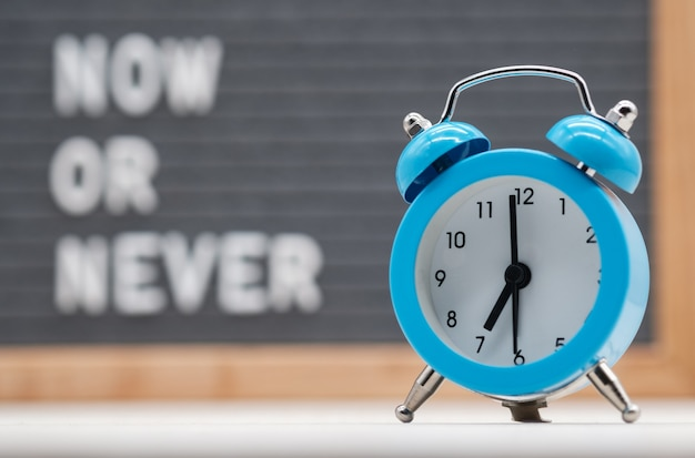 Blue analog alarm clock on english text background now or never . the concept of immediate action