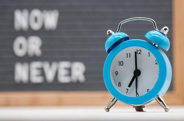지금 또는 결코 영어 텍스트 배경에 파란색 아날로그 알람 시계. 즉각적인 행동의 개념