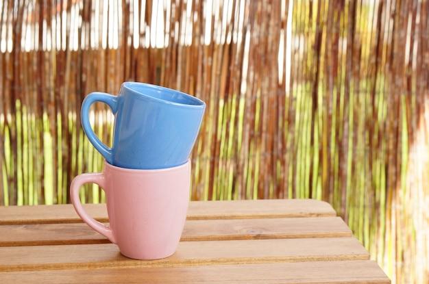 木製のテーブルに青とピンクのマグカップ