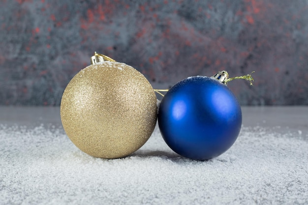 Синие и бежевые декоративные новогодние шары, сидящие в кокосовой пудре на мраморной поверхности