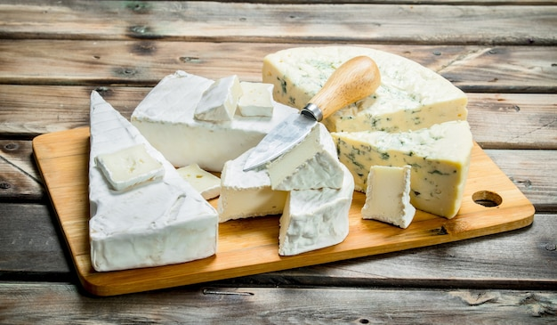 Блю и сыр бри на разделочной доске ножом. на деревянной поверхности.