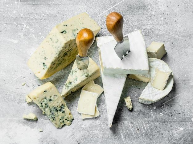 Сыр голубой и бри с ножами. на деревенском фоне.